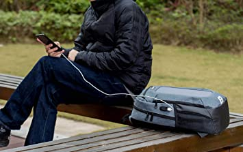 sitting down charging phone with solar a panel backpack
